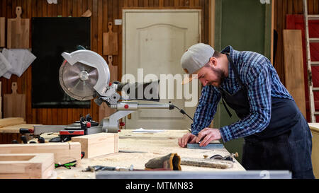 Experienced carpenter in work clothes and small buiness owner working in woodwork workshop, sharpening the tool with whetstone - Stock Photo