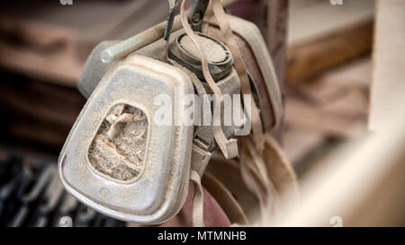 An old carpenter's protective mask for working with paint and for protection against sawdust, covered with sawdust hanging in the workshop - Stock Photo