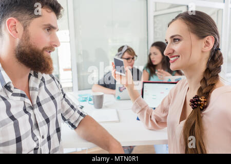 Side view of a creative female freelancer smiling to her co-worker, while making a call on the mobile phone at a shared desk in a relaxed work environ - Stock Photo