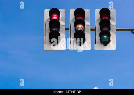 A traffic light and a surveillance camera on a pole mounted on the street. - Stock Photo