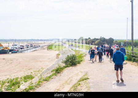 Wells-next-the-Sea, Norfolk, UK. 27th May 2018. People walking along the footpath leading to the beach of Wells on a sunny warm day during the Bank Ho - Stock Photo