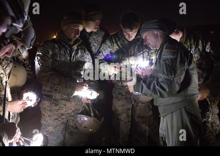 1st Lt. John Adams, right,  36th Airlift Squadron C-130 Hercules navigator, shows Marines from the 3rd Reconnaissance Battalion, 3rd Marine Division, III Marine Expeditionary Force how to operate drop zone indicator lights at Yokota Air Base, Japan, Jan. 11, 2017, during Jump week. III MEF Marines conducted weeklong jump training from a U.S. Air Force C-130H, assigned to the 36 AS. The training not only allowed the Marines to practice jumping, but it also allowed the Yokota aircrews to practice flight tactics and time-package drops. (U.S. Air Force photo by Yasuo Osakabe/Released) - Stock Photo