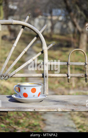 Rustic still life with a cup of tea on a wooden hand-made shelf made from old dried bamboo. Cup of hot tea in the courtyard of the spring garden. Conc - Stock Photo