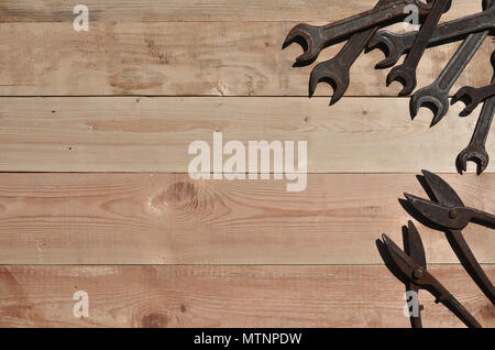 A few rusty spanners and scissors for metal on a wooden background. Obsolete household tools made of rusty metal lie on a wooden table in a workshop.  - Stock Photo