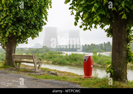 Belleville nuclear power plant on the banks of the Loire in foggy weather with a concrete bench and a fire hydrant on the quay in the foreground. - Stock Photo