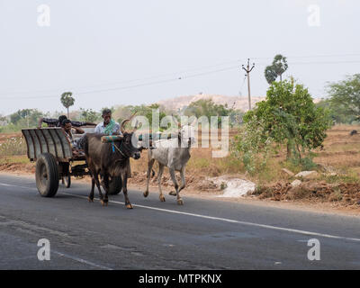 Sivaganga, India - March 11, 2018: Bullock cart and passengers on the move in Tamil Nadu. Such vehicles are a common sight on the state's rural roads - Stock Photo