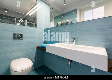 Spacious bathroom with big basin and toilet, blue tiles and mirrors on a walls - Stock Photo