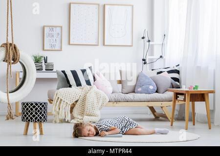 Cute girl in dress lying on floor in modern scandi room