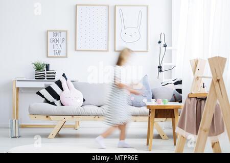 Girl in white dress walking around modern cozy room with coat rack - Stock Photo