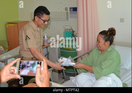 KOTA KINABALU, Malaysia (May 22, 2018) Lance Cpl. Iriwin Matias hands a patient a gift bag during a visit to the Queens Memorial Hospital as part of a community relations project. Matias and more than 60 Marines and Sailors are currently embarked on USNS Millinocket (T-EPF 3) as part of a U.S. 7th Fleet theater security cooperation patrol and will visit several countries in the Indo-Pacific in the coming weeks. (U.S. Navy photo by Mass Communication Specialist 1st Class Chris Krucke/Released) - Stock Photo
