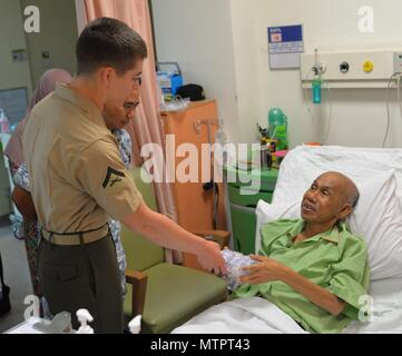 KOTA KINABALU, Malaysia (May 22, 2018) Lance Cpl. Reece Benedict hands a patient a gift bag during a visit to the Queens Memorial Hospital as part of a community relations project. Benedict and more than 60 Marines and Sailors are currently embarked on USNS Millinocket (T-EPF 3) as part of a U.S. 7th Fleet theater security cooperation patrol and will visit several countries in the Indo-Pacific in the coming weeks. (U.S. Navy photo by Mass Communication Specialist 1st Class Chris Krucke/Released) - Stock Photo