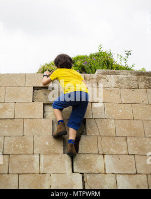 Young boy of ten climbs on a wall. Humpty Dumpty sat on a wall, Humpty Dumpty had a great fall All the king's horses and all the king's men Couldn't p - Stock Photo
