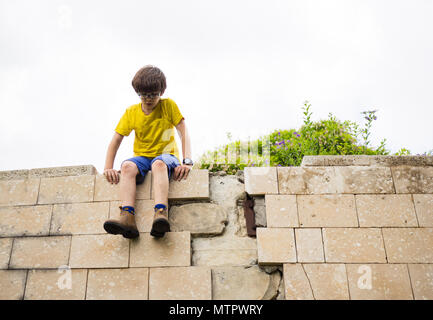 Young boy of ten sites on a wall.  Humpty Dumpty sat on a wall,  Humpty Dumpty had a great fall  All the king's horses and all the king's men  Couldn' - Stock Photo