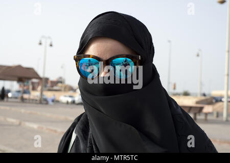 A Saudi woman wearing a black abaya and hijab protects her eyes from the sun with blue sunglasses - Stock Photo