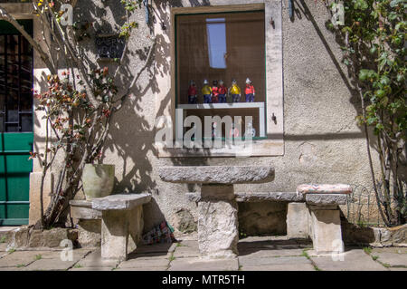 Central Istria, Croatia - Stone benches and table in front of an art gallery housed in an ancient residence in the medieval town of Grisignana - Stock Photo