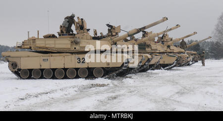 ZAGAN, Poland – M1A2 Abrams Tanks belonging to 1st Battalion, 66th Armored Regiment, 3rd Armored Brigade Combat Team, 4th Infantry Division, line up Jan. 19 prior to beginning the day's gunnery range. The tanks and the Soldiers arrived in Poland earlier this month from Colorado Springs. The arrival of 3rd Arm. Bde. Cmbt. Team marks the start of back-to-back rotations of armored brigades in Europe as part of Operation Atlantic Resolve. The vehicles and the Soldiers will spend the remainder of the month training and making sure their vehicles are in good-working order before deploying across Eas - Stock Photo