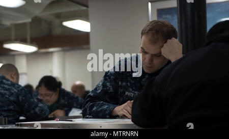 170119-N-BR551-019 BREMERTON, Washington (Jan. 19, 2017) Mass Communication Specialist 1st Class Matthew White, from Dayton, Ohio, takes the Navy-wide chief petty officer advancement exam on USS John C. Stennis' (CVN 74) mess deck. John C. Stennis is currently in port preparing for a planned incremental availability. (U.S. Navy photo by Mass Communication Specialist 3rd Class Dakota Rayburn / Released) - Stock Photo