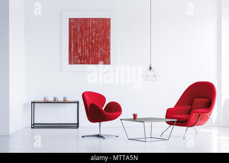 Black metal table with three candles standing in the corner of white room with red armchairs - Stock Photo