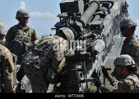 New York National Guard Soldiers assigned to Charlie Battery, 1st Battalion, 258th Field Artillery, load a round into a M777 Howitzer, on Fort Drum, Watertown N.Y., May 22nd, 2018. Soldiers from the 258 spent the past two weeks preparing to fire these weapons, which are much larger, and more powerful than the previous cannon's they used. (N.Y. Army National Guard photo by Spc. Andrew Valenza) - Stock Photo