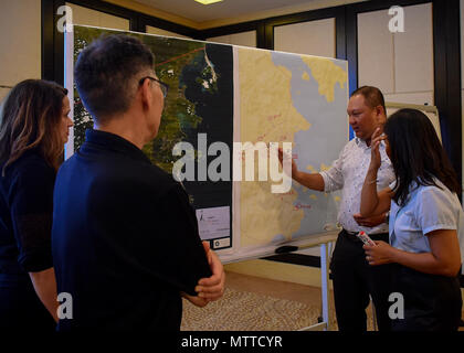180524-N-QV906-0077 NHA TRANG, Vietnam (May 24, 2018) Oceana Francis, Ph.D. (left), and Karl Kim, Ph.D., of the National Disaster Preparedness Training Center at the University of Hawaii, discuss environmental obstacles when dealing with disaster recovery efforts with Vietnamese counterparts during a Civil Engineering and Disaster Recovery Symposium. Mercy is currently deployed in support of Pacific Partnership 2018 (PP18). PP18's mission is to work collectively with host and partner nations to enhance regional interoperability and disaster response capabilities, increase stability and securit - Stock Photo