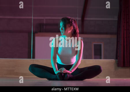Female dancer relaxing in dance studio - Stock Photo
