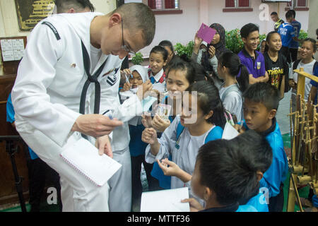 KOTA KINABALU, MALAYSIA (May 25, 2018) Musician 2nd Class Holden Moyer of the U.S. 7th Fleet Band signs autographs for students at SMK Tamparuli High School in Kota Kinabalu, Malaysia after a performance. The band is supporting a U.S. 7th Fleet theater security cooperation mission and will be traveling to several Indo-Pacific countries in the coming weeks. (U.S. Navy photo by Mass Communication Specialist 2nd Class Chase Hawley/Released) - Stock Photo