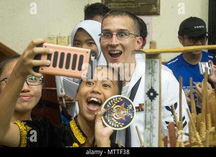 KOTA KINABALU, MALAYSIA (May 25, 2018) Musician 2nd Class Holden Moyer of the U.S. 7th Fleet Bandtakes a photo with a member of the SMK Tamparuli bamboo orchestra after a performance at SMK Tamparuli High School  in Kota Kinabalu, Malaysia. The band is supporting a U.S. 7th Fleet theater security cooperation mission and will be traveling to several Indo-Pacific countries in the coming weeks. (U.S. Navy photo by Mass Communication Specialist 2nd Class Chase Hawley/Released) - Stock Photo