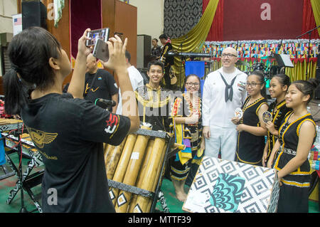 KOTA KINABALU, MALAYSIA (May 25, 2018) Musician 1st Class Stephen Hux of the U.S. 7th Fleet Band takes a picture with members of the SMK Tamparuli bamboo orchestra after a performance at SMK Tamparuli High School  in Kota Kinabalu, Malaysia. The band is supporting a U.S. 7th Fleet theater security cooperation mission and will be traveling to several Indo-Pacific countries in the coming weeks. (U.S. Navy photo by Mass Communication Specialist 2nd Class Chase Hawley/Released) - Stock Photo