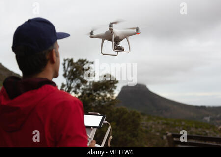 Man operating a flying drone in countryside - Stock Photo