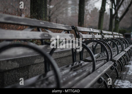 Row of World's Fair park benches drying from rain in Hudson River Park in New York City, overlooking the Hudson River. - Stock Photo