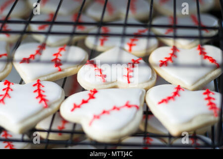 Heart shaped baseball sugar cookies cooling off on racks in the bakery kitchen - Stock Photo