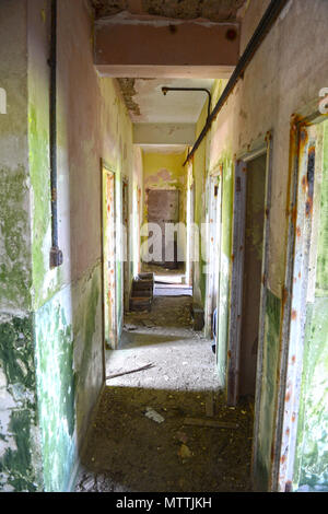 Inside an old derelict vandalised building with paint peeling graffiti and total desolation with broken glass windows and no doors - Stock Photo