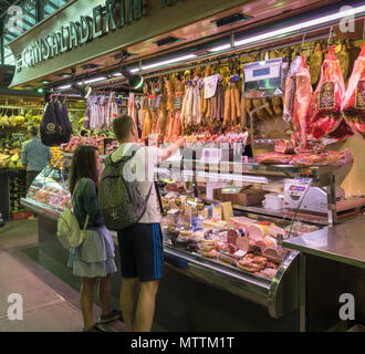 Young couple shopping at a food stall in Mercat de la Boqueria, Barcelona, Catalunya, Spain. - Stock Photo