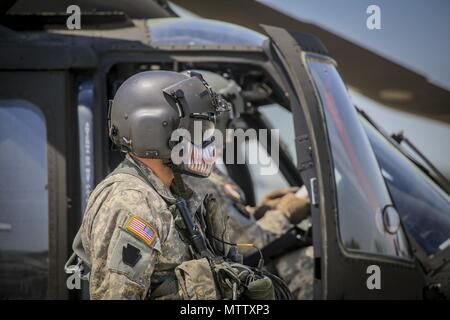 New Jersey Army National Guard Sgt. Daniel Rivera, a UH-60L Black Hawk helicopter crew chief from the 1st Assault Helicopter Battalion, 150th Aviation Regiment, prepares his aircraft for a flight at Joint Base McGuire-Dix-Lakehurst, N.J. May 15, 2018, May 15, 2018. (U.S. Air National Guard photo by Master Sgt. Matt Hecht). () - Stock Photo
