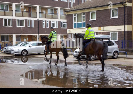 Two Metropolitan Policemen riding horses that are trotting through a puddle on the way to the stables in Bow, Tower Hamlets, London - Stock Photo