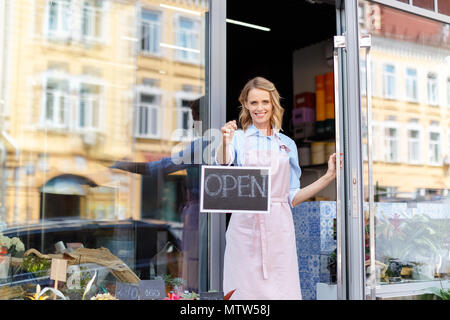 attractive young female florist in apron holding open sign and smiling at camera - Stock Photo