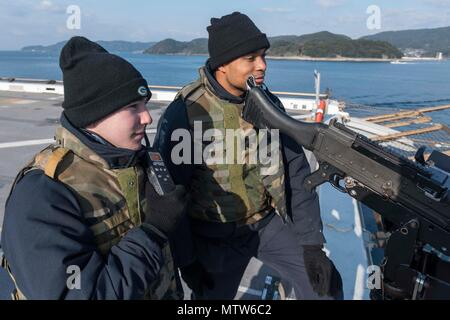 SASEBO, Japan (Jan. 25, 2017) Logistics Specialist Seaman Manuel Brown and Aviation Boatswain's Mate (Handling) Airman Amado Banos Derrickson stand watch on the flight deck aboard the amphibious transport dock ship USS Green Bay (LPD 20) during a sea and anchor evolution. Green Bay is on a routine patrol, operating in the Indo-Asia-Pacific region to enhance partnerships and be a ready response force for any type of contingency. (U.S. Navy photo by Mass Communication Specialist 2nd Class Kaleb R. Staples/Released) - Stock Photo