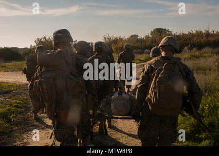 U.S. Marines assigned to Special Purpose Marine Air Ground Task Force - Crisis Response – Africa carry notionally injured personnel during a mission readiness exercise at Naval Station Rota, Spain, Jan. 21, 2017. During the exercise, air, ground and logistics elements conducted integrated planning and execution of the Tactical Recovery of Aircraft and Personnel operations, a primary mission of the SPMAGTF. - Stock Photo