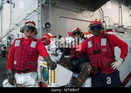 170127-N-UE100-076  ATLANTIC OCEAN (Jan. 27, 2017) Sailors from crash and salvage division pose for a photo on the flight deck of the amphibious assault ship USS Bataan (LHD 5). Crash stands by in case of fire or emergency. Bataan is underway conducting Composite Training Unit Exercise (COMPTUEX) with the Bataan Amphibious Ready Group in preparation for an upcoming deployment. (U.S. Navy photo by Mass Communication Specialist 3rd Class Caleb Strong/Released) - Stock Photo