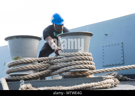 OKINAWA, Japan (Jan 30, 2017) Boatswain's Mate Seaman Kelvin Wagner, from Houston, secures a mooring line on the forecastle of the amphibious transport dock ship USS Green Bay (LPD 20) as the ship moors in Okinawa, Japan.  Green Bay is on a routine patrol, operating in the Indo-Asia-Pacific region to enhance partnerships and be a ready-response force for any type of contingency. (U.S. Navy photo by Mass Communication Specialist 2nd Class Kaleb R. Staples/Released) - Stock Photo