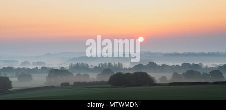 Misty sunrise in spring over the Warwickshire countryside near Stratford Upon Avon. Warwickshire, UK. Panoramic - Stock Photo