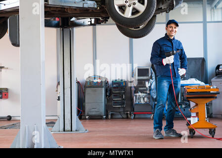 Portrait of a smiling mechanic at work in his garage - Stock Photo