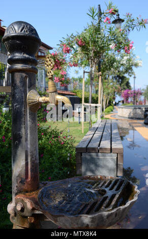 The bronze tap with flowing water on a hot summer day. Vintage faucet in a park - Stock Photo