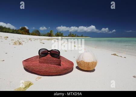 Summer hat and coconut on tropical sandy beach, Christmas Island, Kiribati - Stock Photo