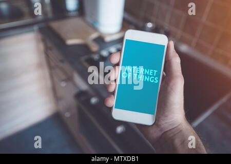 Internet of things, smartphone connecting with ceramic stove top. Smart home kitchen appliance connecting with mobile phone and exchanging data. - Stock Photo