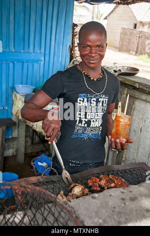 GRAND BASSAM, IVORY COAST, AFRICA. May 1, 2013. Young African man cooks meat on a grill in a beach side cafe in Grand Bassam. - Stock Photo