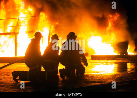 JOHANNESBURG, SOUTH AFRICA - MAY, 2018 Firefighters kneeling in front of burning structure during fighting training exercise - Stock Photo
