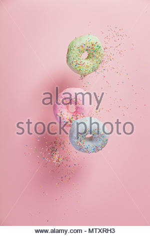 Sweet and colourful doughnuts with sprinkles falling or flying in motion against pastel pink background - Stock Photo