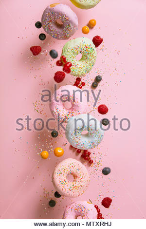 Sweet and colourful doughnuts with sprinkles and berries falling or flying in motion against pink pastel background - Stock Photo