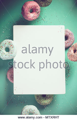 Sweet and colourful doughnuts with sprinkles falling or flying in motion against blue pastel background - Stock Photo